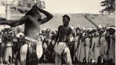 One Man Wielding A Cane Against Another Man During A Sharo Festival